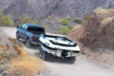 A truck towing a boat up a dirt hill in Australia